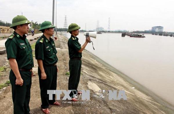 Các chiến sĩ biên phòng tỉnh Thái Bình kêu gọi các tàu thuyền vào nơi tránh trú bão an toàn. Ảnh: THẾ DUYỆT – TTXVN