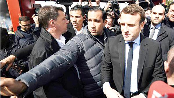 Ông Alexandre Benalla (người vươn tay che chắn) là vệ sĩ thân cận của Tổng thống Pháp Emmanuel Macron (phải). Ảnh: AP