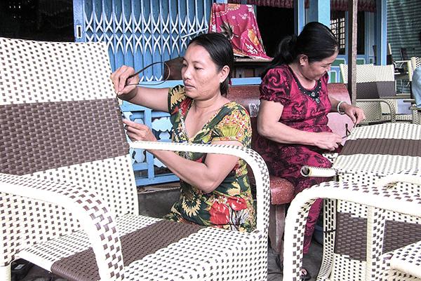 Phụ nữ xã Trung Hưng, huyện Cờ Đỏ đan sản phẩm ghế bằng dây nhựa. Ảnh: ANH PHƯƠNG