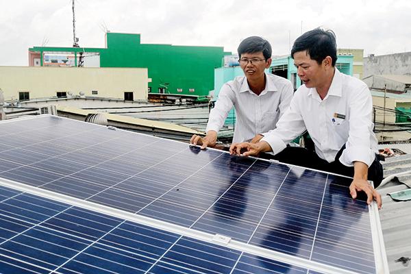 Cán bộ ngành điện kiểm tra hệ thống điện năng lượng mặt trời hòa lưới áp mái của một doanh nghiệp ở quận Ninh Kiều. Ảnh: M.HOA