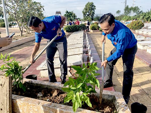 Cán bộ, đoàn viên quận Ô Môn trồng hoa trong khuôn viên Nghĩa trang Liệt sĩ quận. Ảnh: CTV