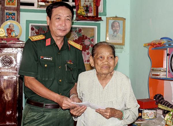 Thượng tá Nguyễn Khắc Tuyên, Chủ nhiệm Kỹ thuật Bộ CHQS thành phố trao quà cho Mẹ VNAH Nguyễn Thị Út Chót. Ảnh: PHẠM TRUNG