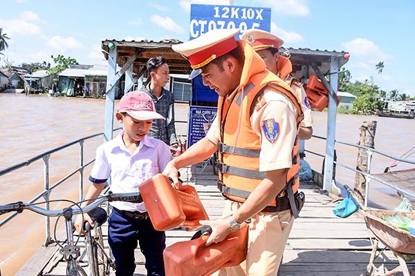 CSGT Công an huyện Phong Điền hướng dẫn người đi đò sử dụng dụng cụ nổi cứu sinh cầm tay khi đi trên phương tiện thủy. Ảnh: XUÂN ĐÀO
