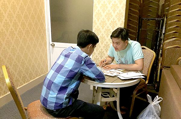 Tiếp cận viên hướng dẫn khách hàng sử dụng test HIV bằng dịch miệng. Ảnh: H.HOA