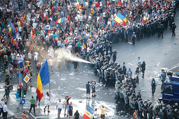 Cảnh sát chống bạo động Romania xịt vòi rồng vào người biểu tình tại Bucharest hôm 10-8. Ảnh: Reuters