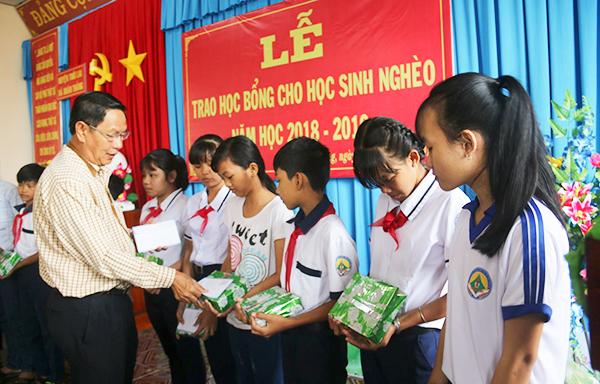 Ông Lê Văn Tâm trao học bổng cho học sinh vượt khó học tốt xã Xuân Thắng, huyện Thới Lai. Ảnh T.V
