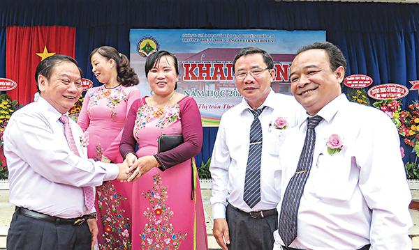 Ông Trần Quốc Trung (bìa trái), Bí thư Thành ủy trò chuyện với lãnh đạo địa phương, Ban Giám hiệu Trường THCS Thị trấn Thới Lai dịp đầu năm học mới.