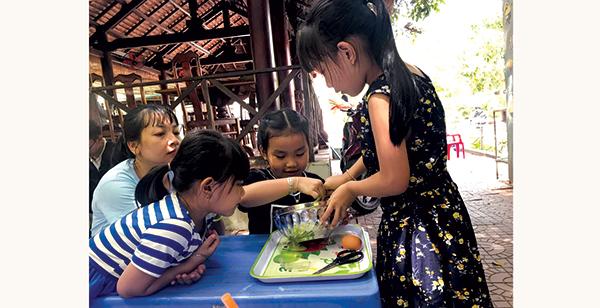 Có những trải nghiệm chỉ thực hiện cùng con gái nên nhiều mẹ rất cưng các cô công chúa nhỏ. (Trong ảnh: Một phụ huynh dạy con và cháu gái làm bánh tại khu vui chơi ở quận Ninh Kiều). Ảnh: KIỀU CHINH