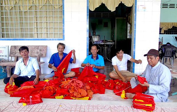 Ông Võ Văn Chính (giữa) cùng các cán bộ ấp xếp cờ Tổ quốc. Ảnh: NGUYỄN HUY