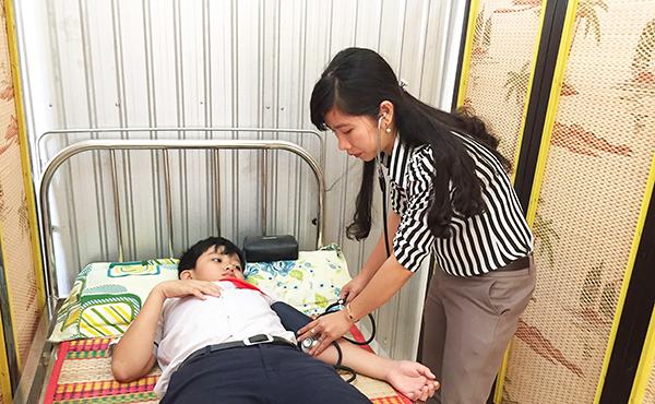 Cán bộ y tế Trường THCS Thới Long chăm sóc sức khỏe học sinh. Ảnh: CHẤN HƯNG