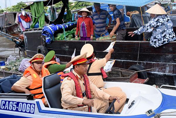 Cảnh sát đường thủy tham gia phát tờ rơi tuyên truyền ATGT đường thủy cho người dân khu vực chợ nổi Cái Răng. Ảnh: XUÂN ĐÀO