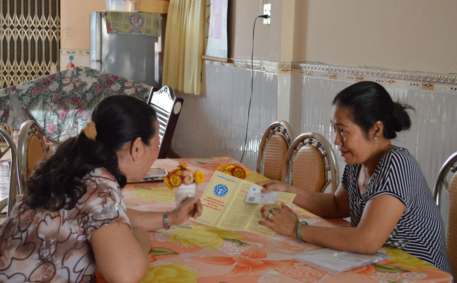 Cộng tác viên tuyên truyền chính sách BHYT cho người dân tại huyện Phong Điền. Ảnh: H.Hoa