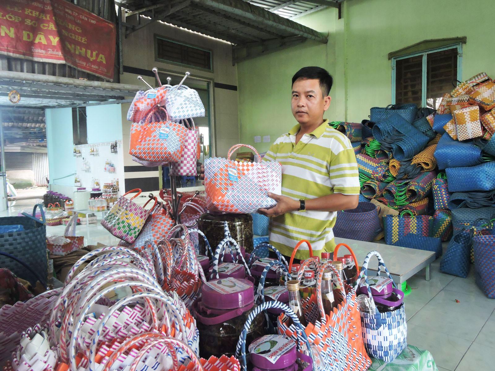 Anh Trần Công Hào giới thiệu những giỏ đan từ dây nhựa. Ảnh: MỸ TÚ