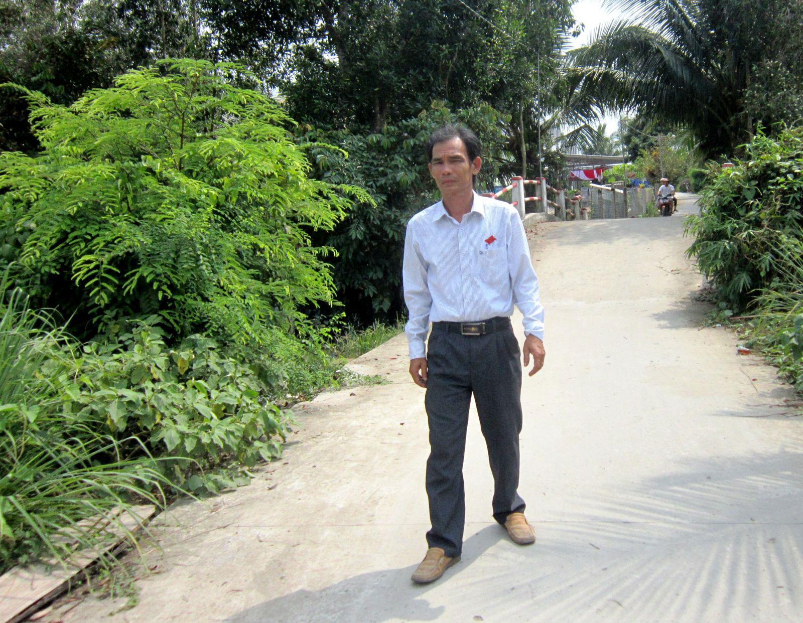 Ông Trần Quang Phục trên con đường được nâng cấp, mở rộng từ phần đất mà gia đình ông đã hiến. Ảnh: CÁT ĐẰNG