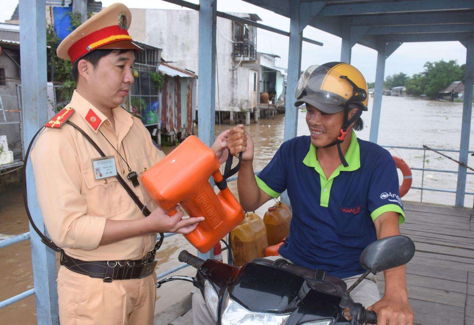 CSGT Công an huyện Vĩnh Thạnh hướng dẫn người đi đò sử dụng dụng cụ nổi cứu sinh cầm tay. Ảnh: XUÂN ĐÀO