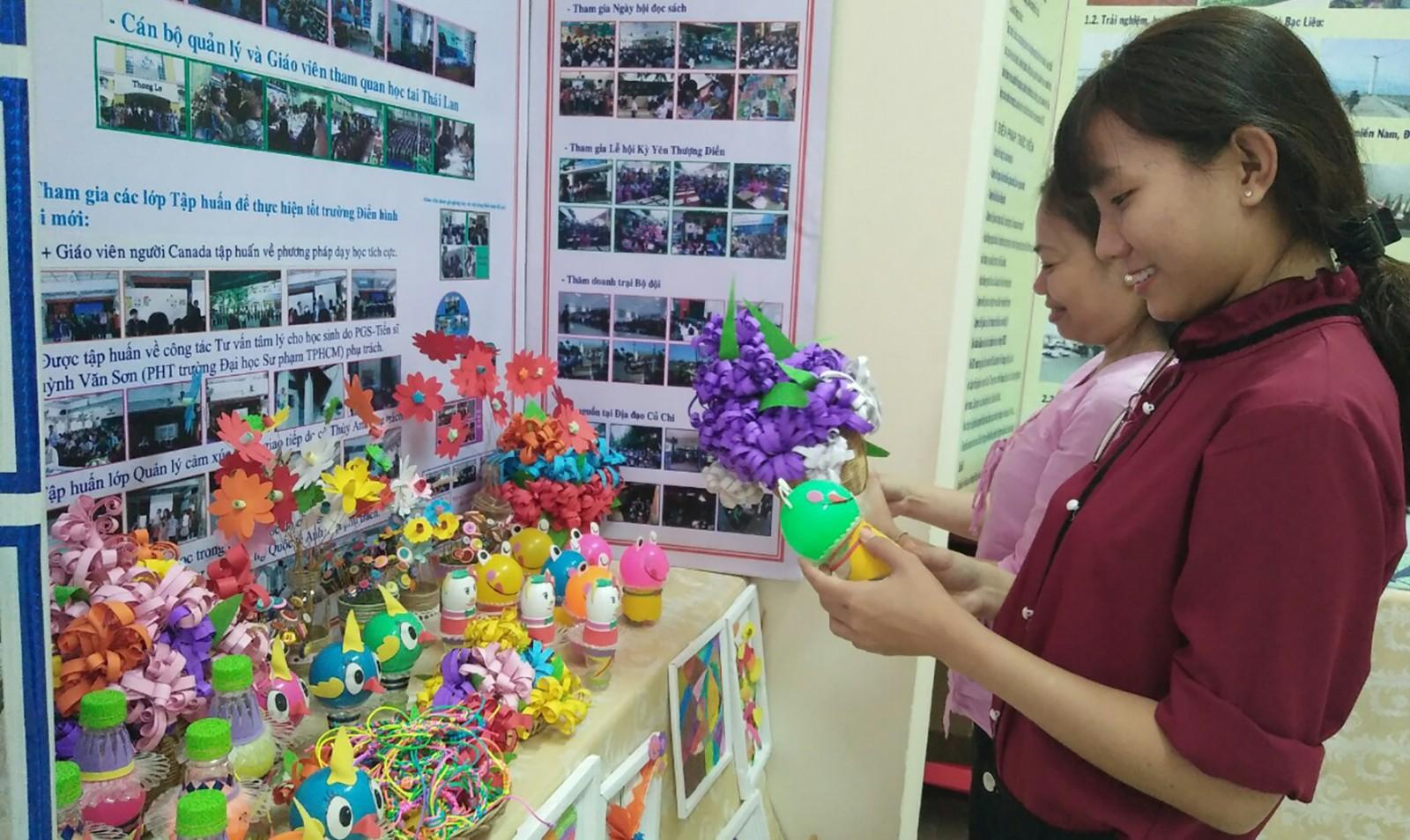 Đại biểu tham quan gian hàng trưng bày sản phẩm của các đơn vị, trường học thực hiện Trường Điển hình đổi mới. Ảnh: BÍCH NGỌC