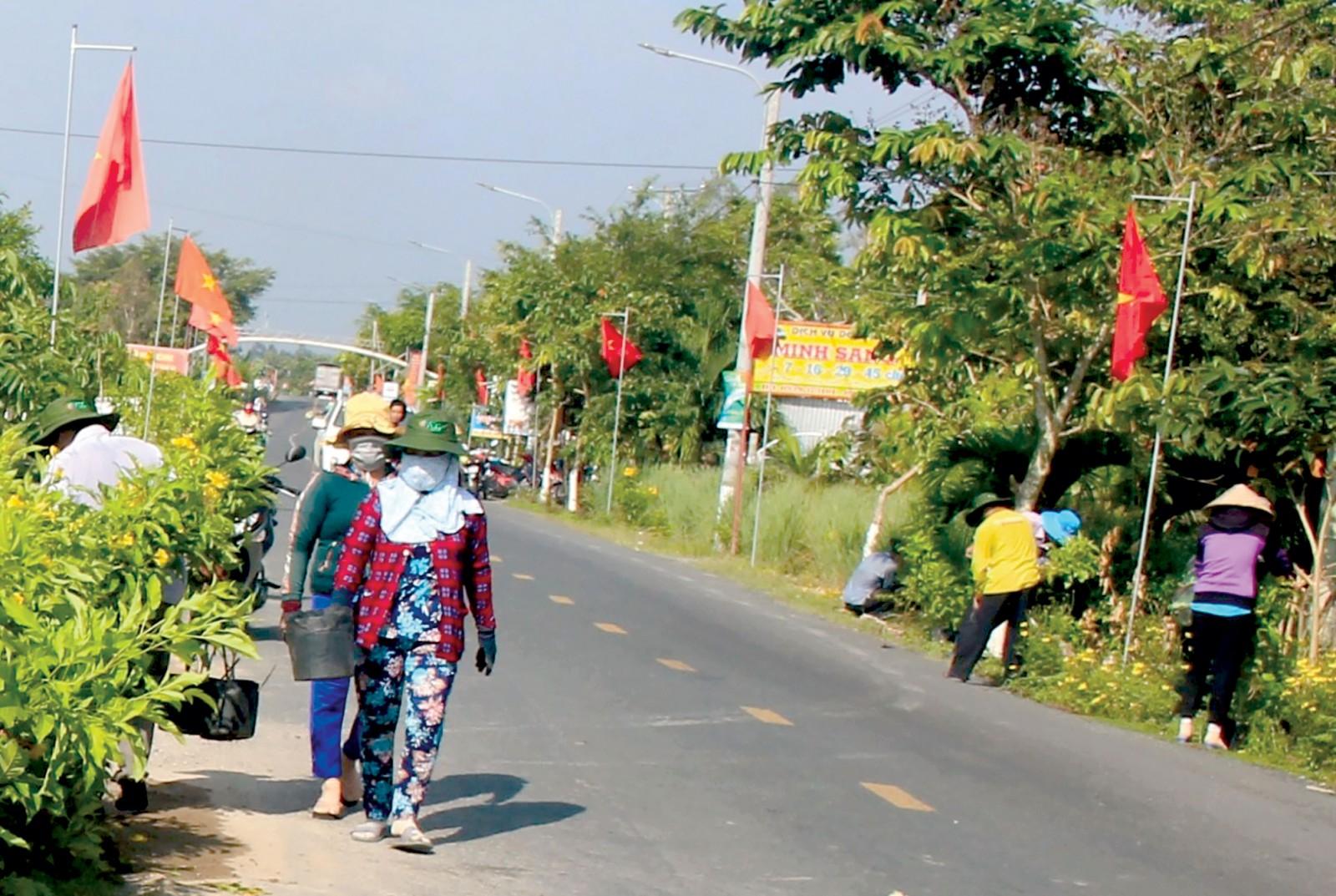 Người dân trên địa bàn xã Đông Thắng, huyện Cờ Đỏ tham gia trồng và chăm sóc cây xanh (cây hoàng yến) dọc theo tỉnh lộ 922, đoạn đi qua địa bàn xã. Ảnh: HÀ VĂN