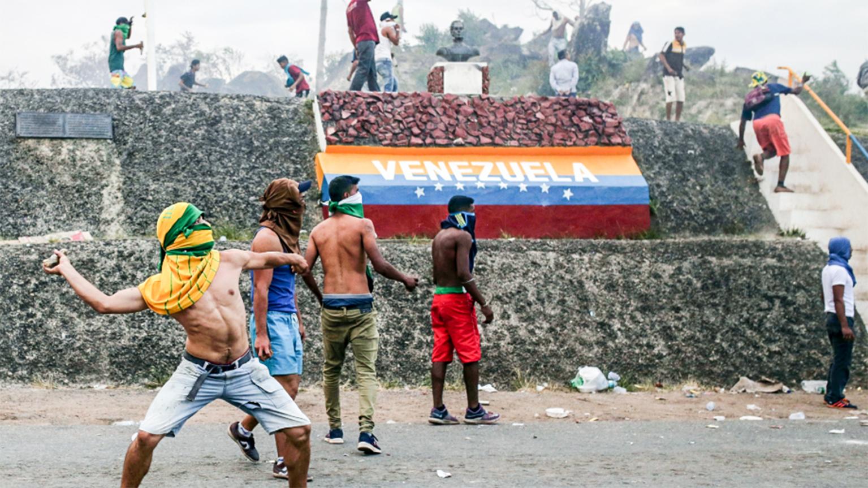 Người biểu tình Venezuela ném đá vào lực lượng an ninh tại biên giới nước này với Brazil hôm 23-2. Ảnh: AP