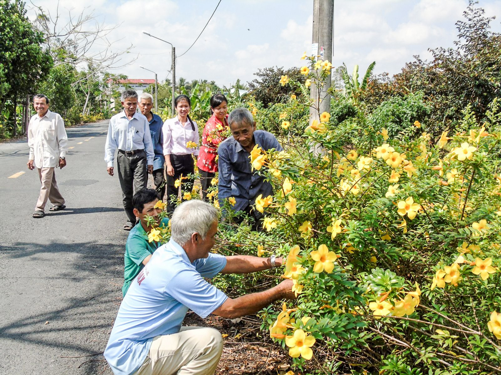Các cán bộ xã Trường Long cùng nhân dân vệ sinh môi trường, xây dựng tuyến đường đẹp. Ảnh: THANH THY
