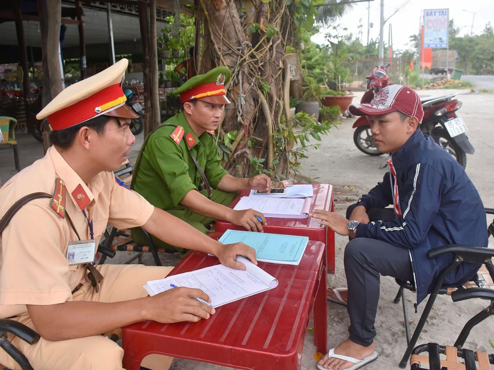 Cảnh sát giao thông -trật tự Công an huyện Vĩnh Thạnh lập biên bản trường hợp chưa đủ tuổi điều khiển xe phân khối lớn trên đường tỉnh 919, thuộc thị trấn Vĩnh Thạnh. Ảnh: XUÂN ĐÀO