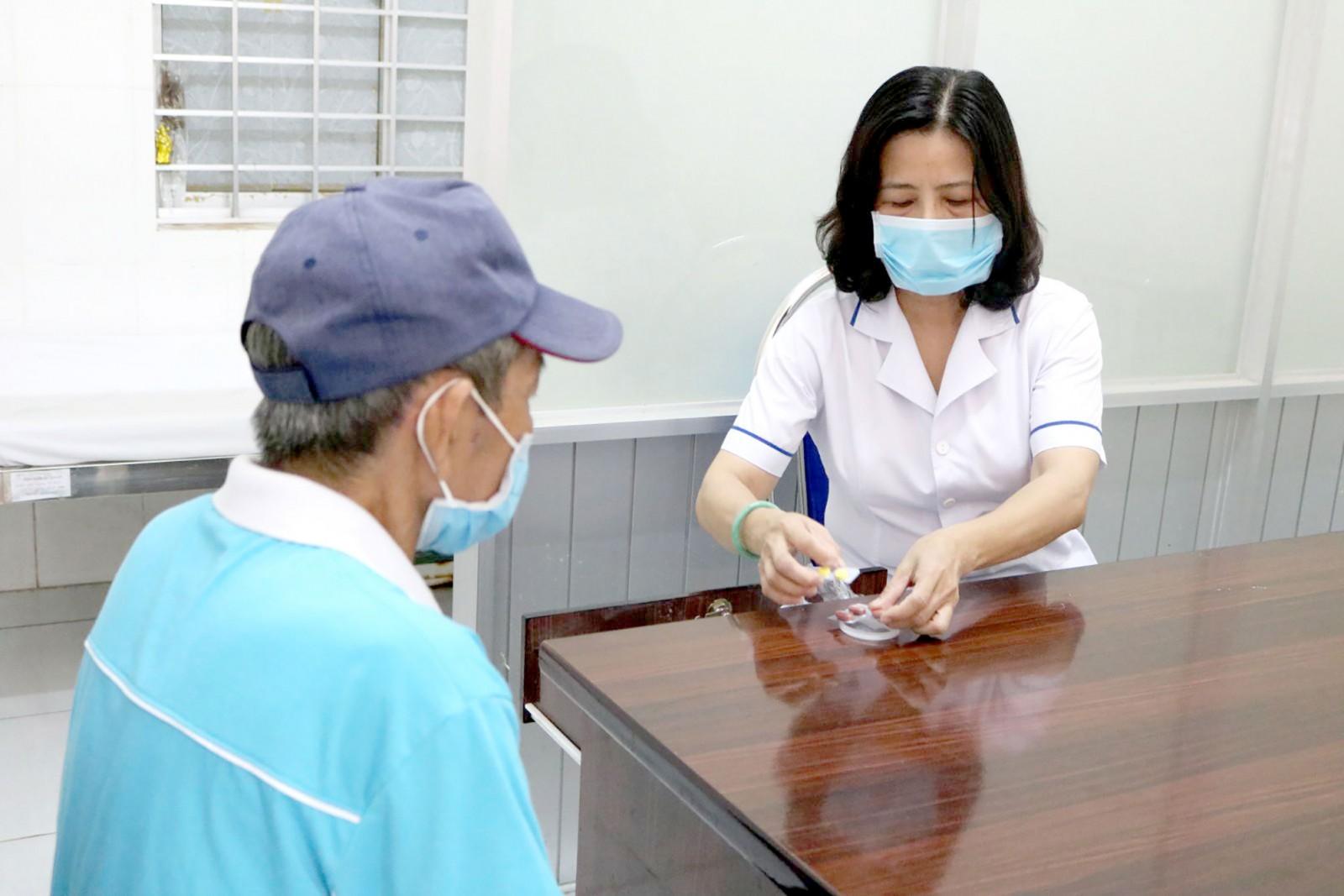 Cán bộ y tế phường An Cư, quận Ninh Kiều, cấp thuốc và tư vấn bệnh nhân lao dùng thuốc.