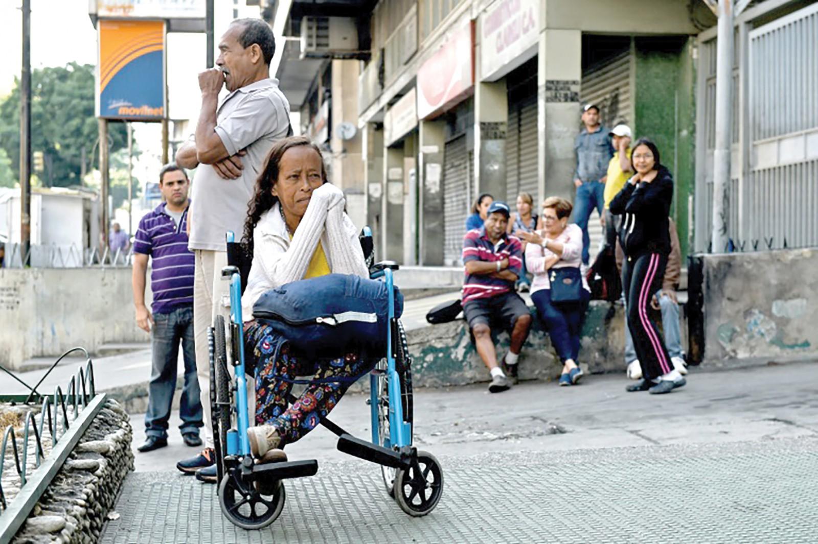 Bệnh nhân chờ bên ngoài một bệnh viện đóng cửa do mất điện ở Caracas. Ảnh: AFP