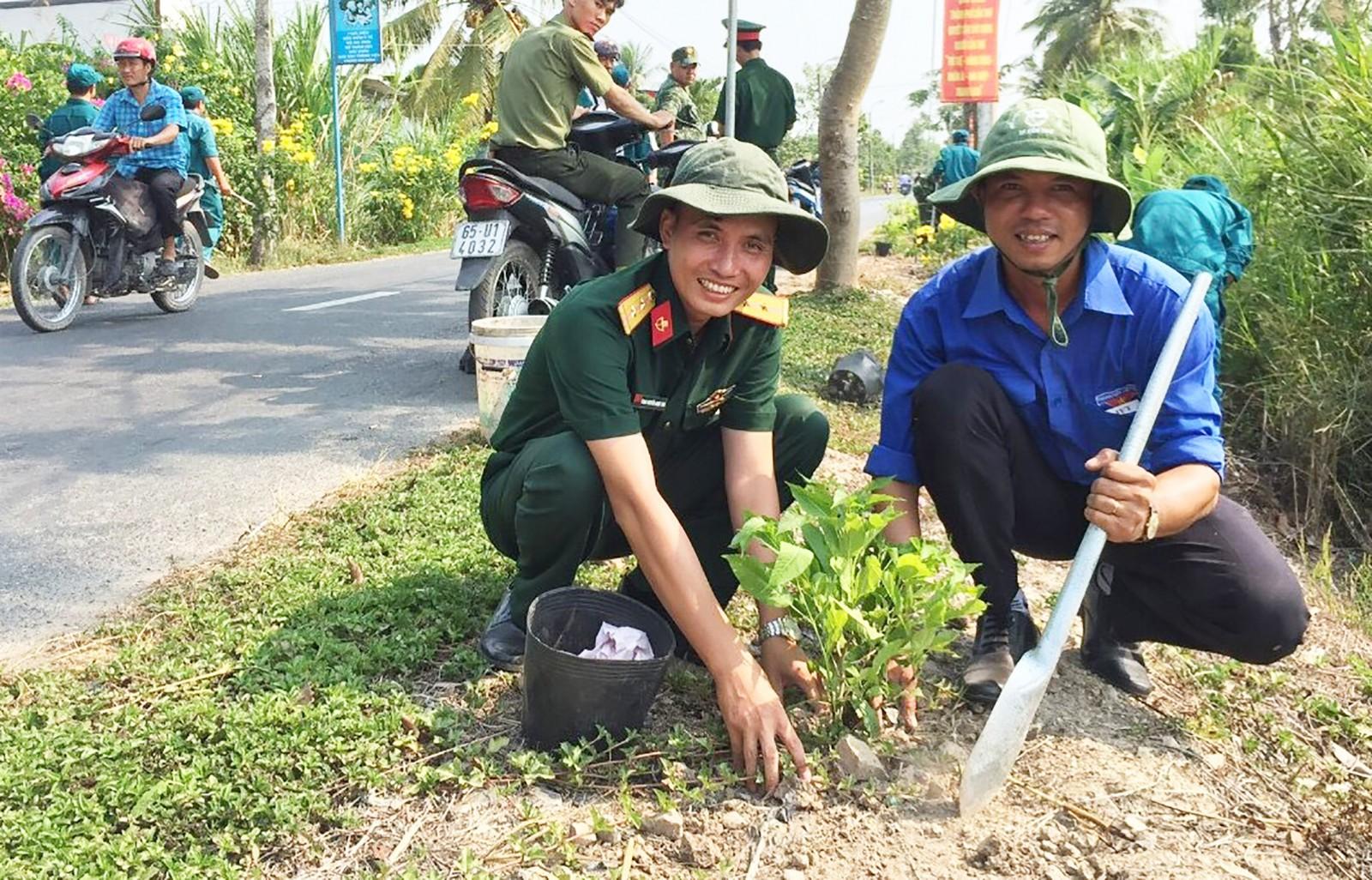 Anh Bùi Phước Thiện (bìa phải) tham gia trồng hoa, vệ sinh các tuyến đường trên địa bàn phường. Ảnh: CHUNG CƯỜNG