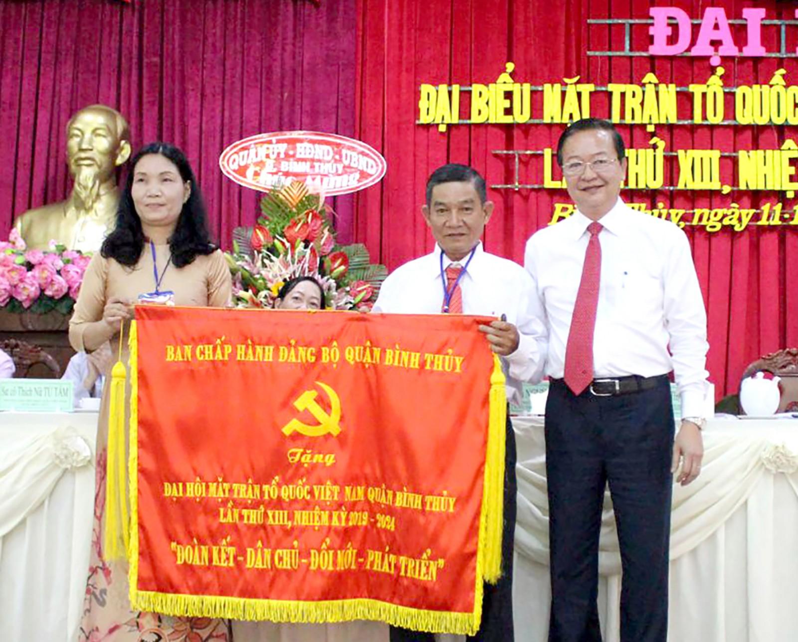 Đồng chí Lê Tấn Thủ, Bí thư Quận ủy Bình Thủy (bìa phải) trao bức trướng của Ban Chấp hành Đảng quận chúc mừng đại hội Mặt trận quận. Ảnh: TÂM KHOA
