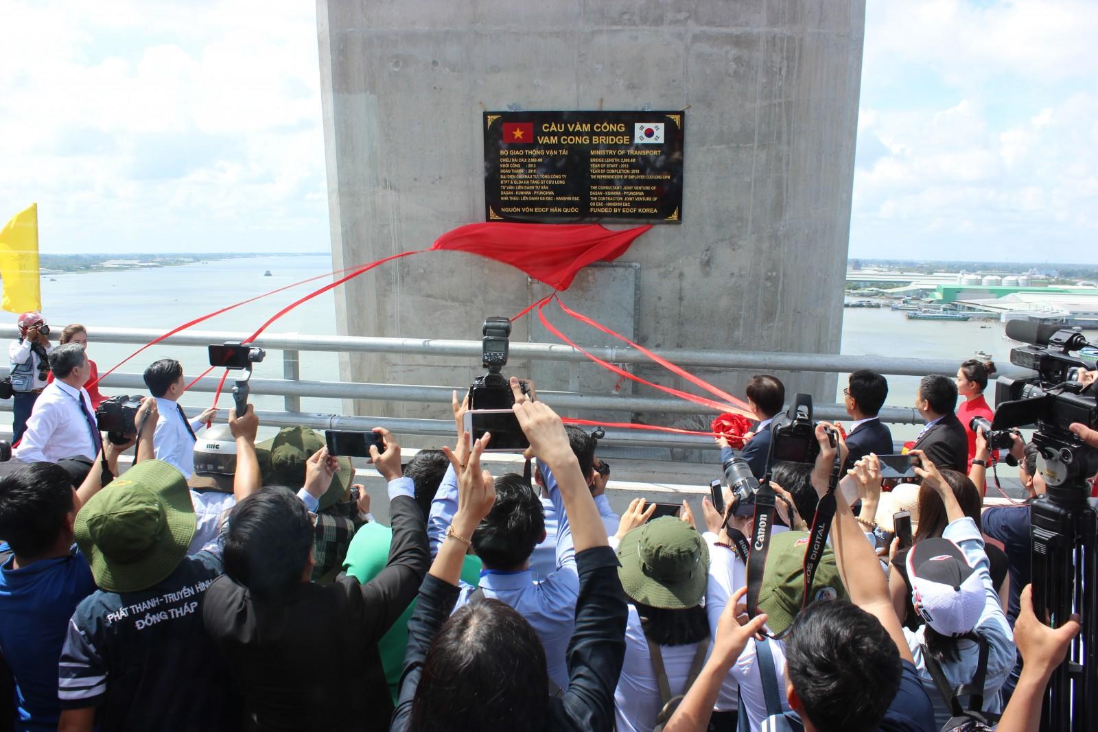Đại biểu thực hiện nghi thức gỡ bảng tên cầu Vàm Cống. Ảnh: T.H