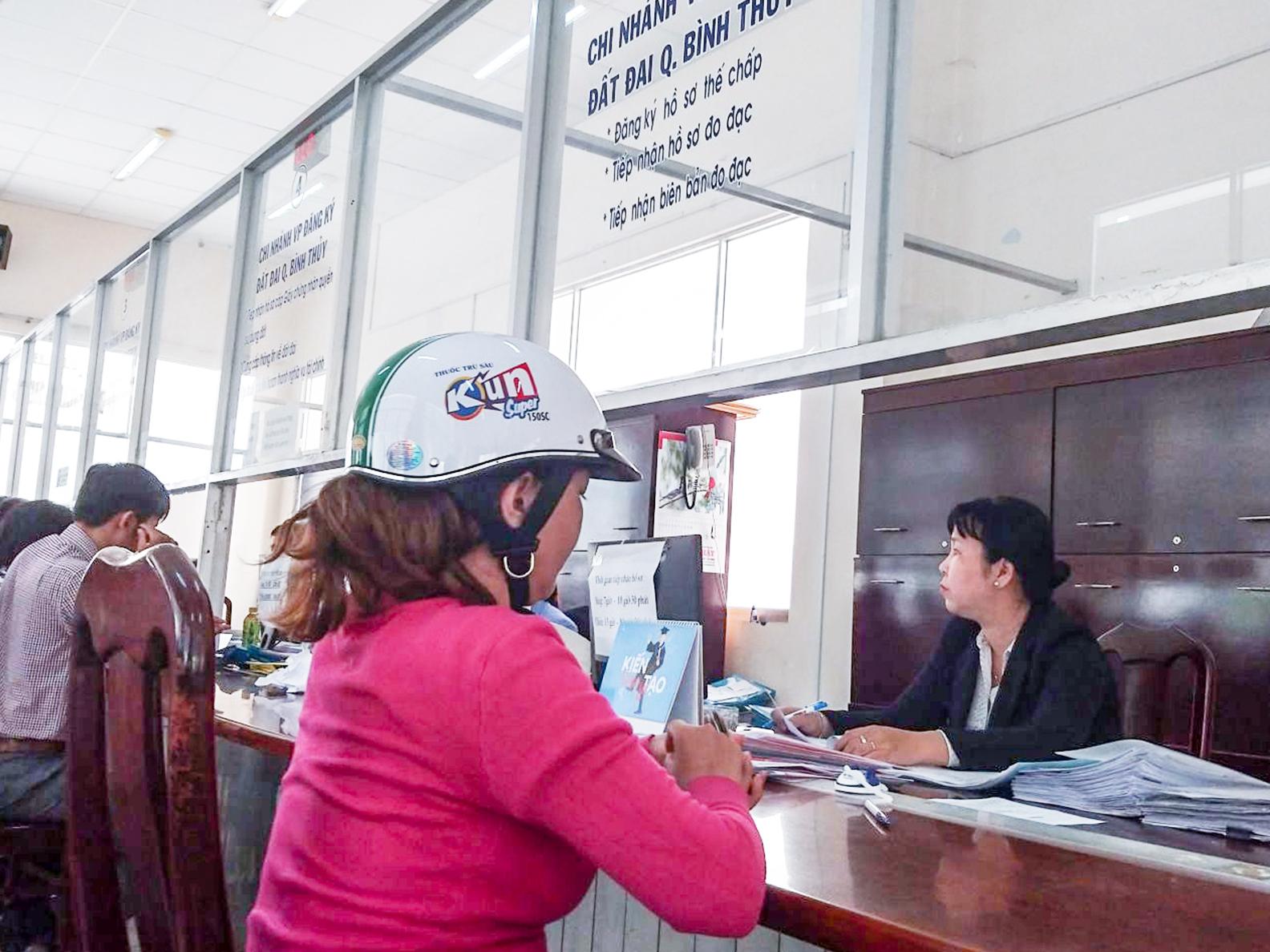 Người dân thực hiện thủ tục hành chính tại Bộ phận một cửa, UBND quận Bình Thủy. Ảnh: MINH HUYỀN