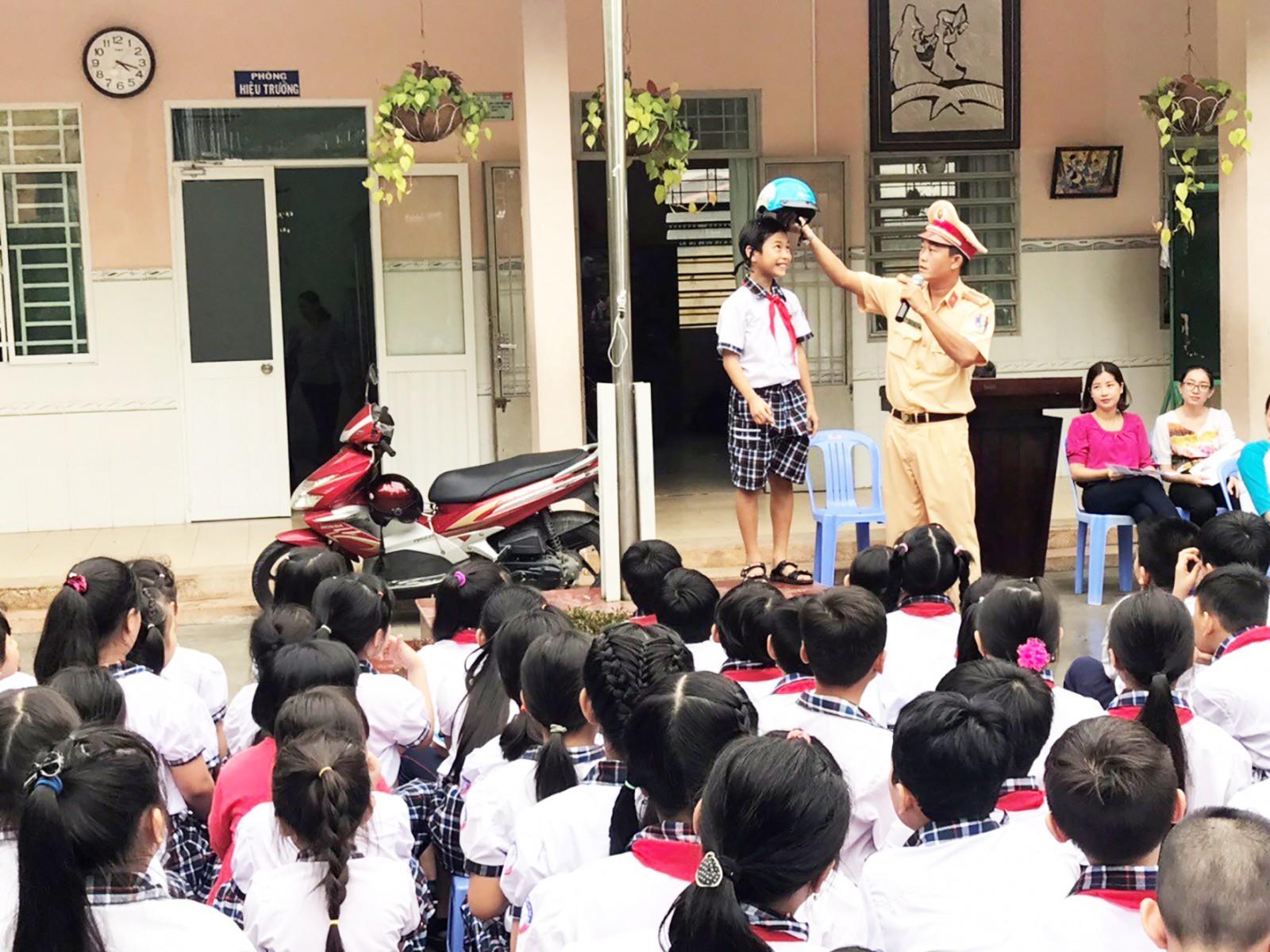 Học sinh Trường Tiểu học Kim Đồng, quận Ninh Kiều được hướng dẫn cách đội nón bảo hiểm đúng quy cách và an toàn. Ảnh do Quận đoàn Ninh Kiều cung cấp.