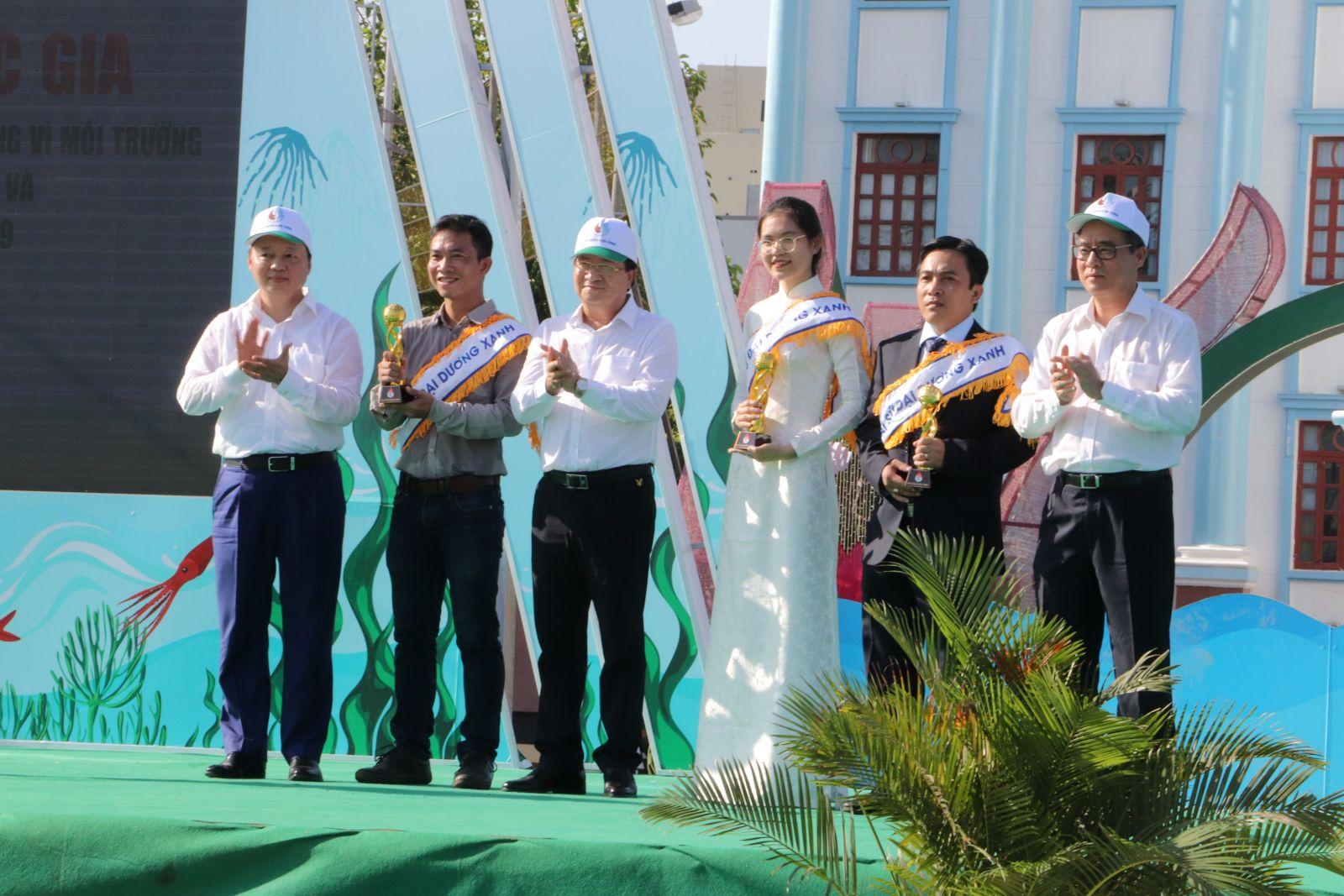 Phó Thủ tướng Trịnh Đình Dũng, Bộ trưởng Bộ TN&MT Trần Hồng Hà trao cúp cho 3 đại sứ Đại dương xanh. Ảnh: N.H