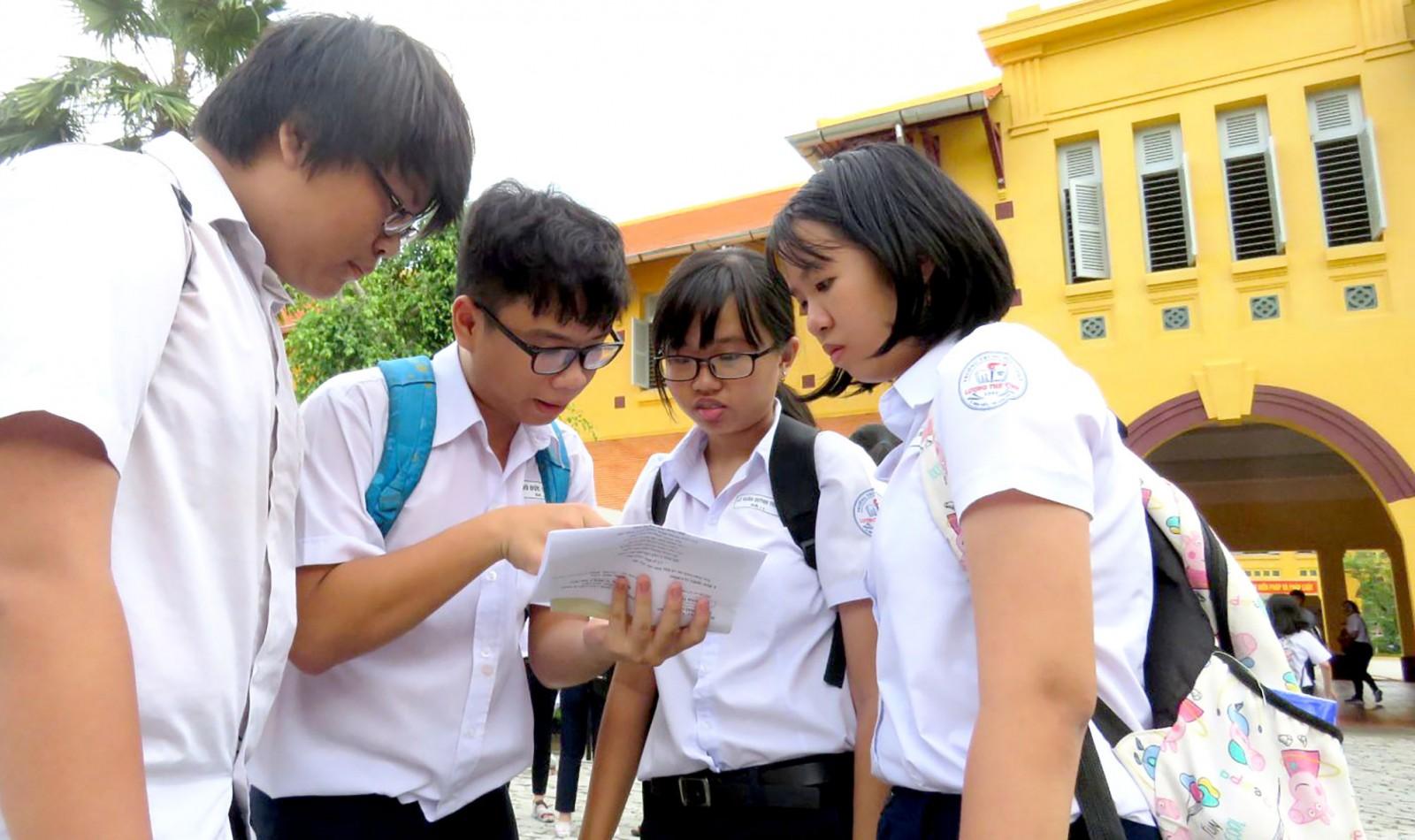 Thí sinh trao đổi bài thi, sau giờ thi môn Ngữ văn, tại điểm thi Trường THPT Châu Văn Liêm.