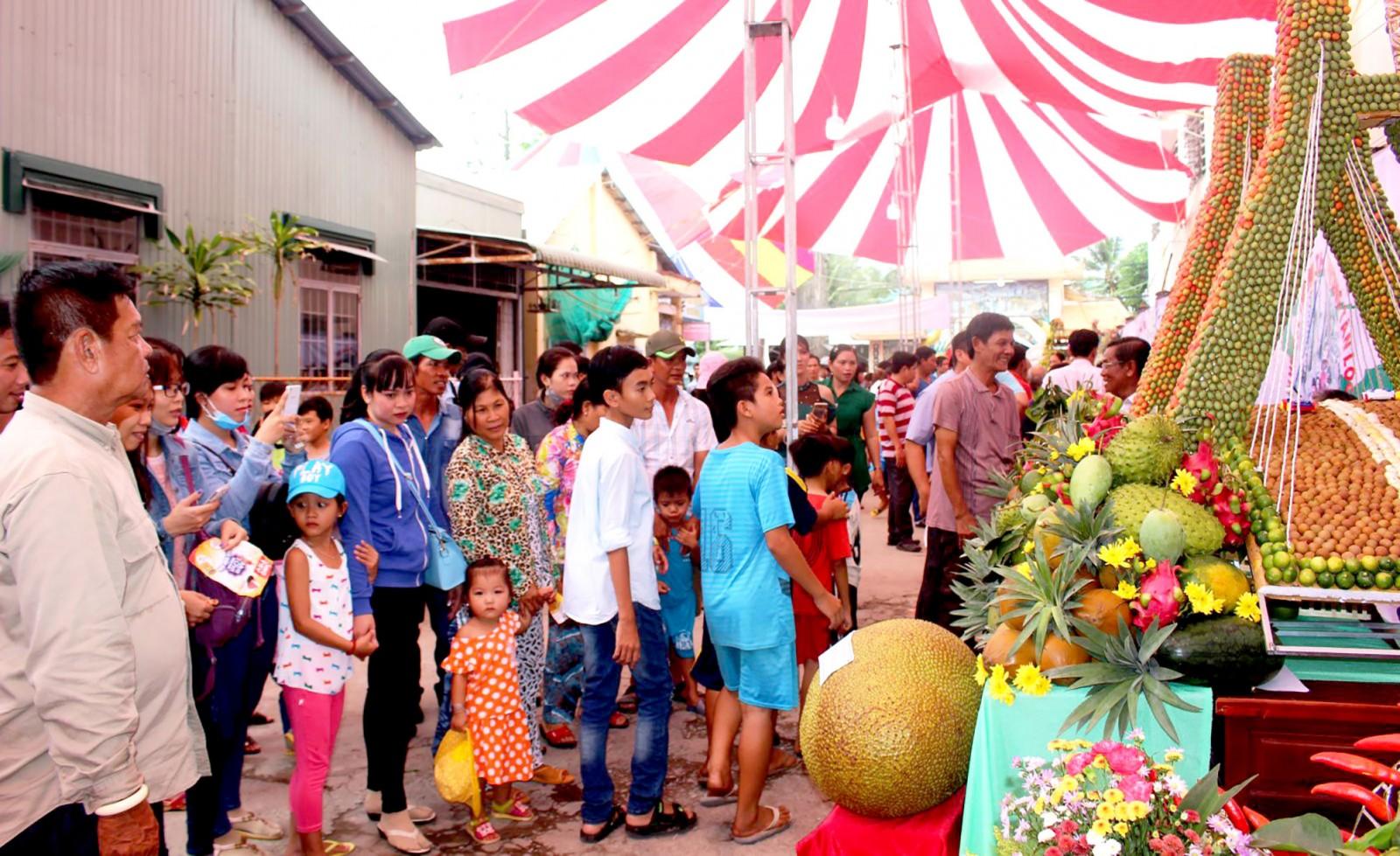Khách tham quan thích thú trước những mâm trái cây được trang trí, tạo hình nghệ thuật đặc sắc và củ quả lạ tại lễ hội hằng năm. Ảnh: LỆ THU