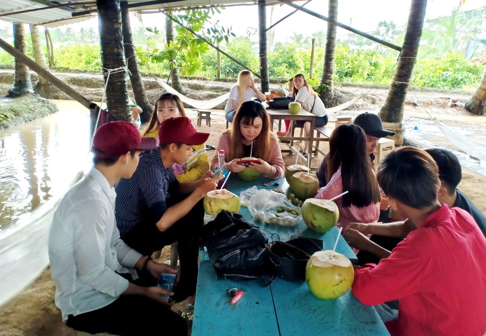 Vườn dừa là một trong những điểm đến lý tưởng khi đến Tân Lộc. Trong ảnh: khách thưởng thức dừa tươi tại vườn dừa.