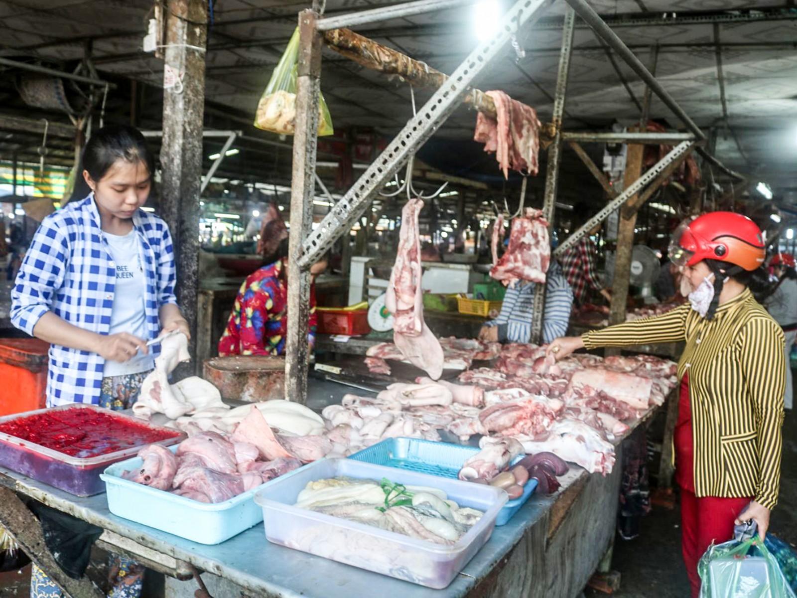 Nhiều người tiêu dùng vẫn đang mua và sử dụng thịt heo bình thường cho bữa ăn hằng ngày. Trong ảnh: Mua, bán thịt heo tại chợ  Phong Điền, TP Cần Thơ.