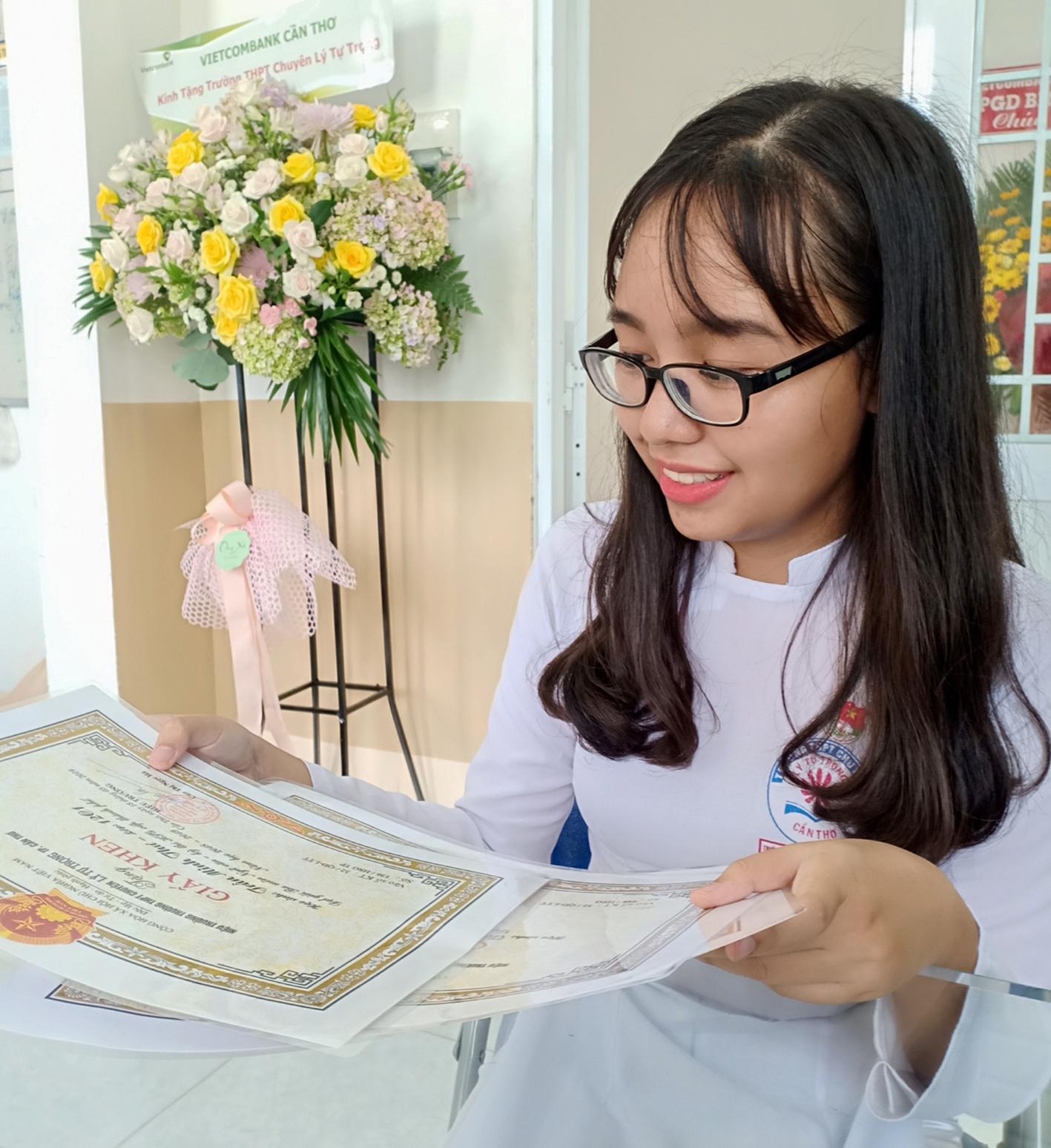 Trần Minh Thư và các giấy khen được nhận vào lễ tổng kết năm học.