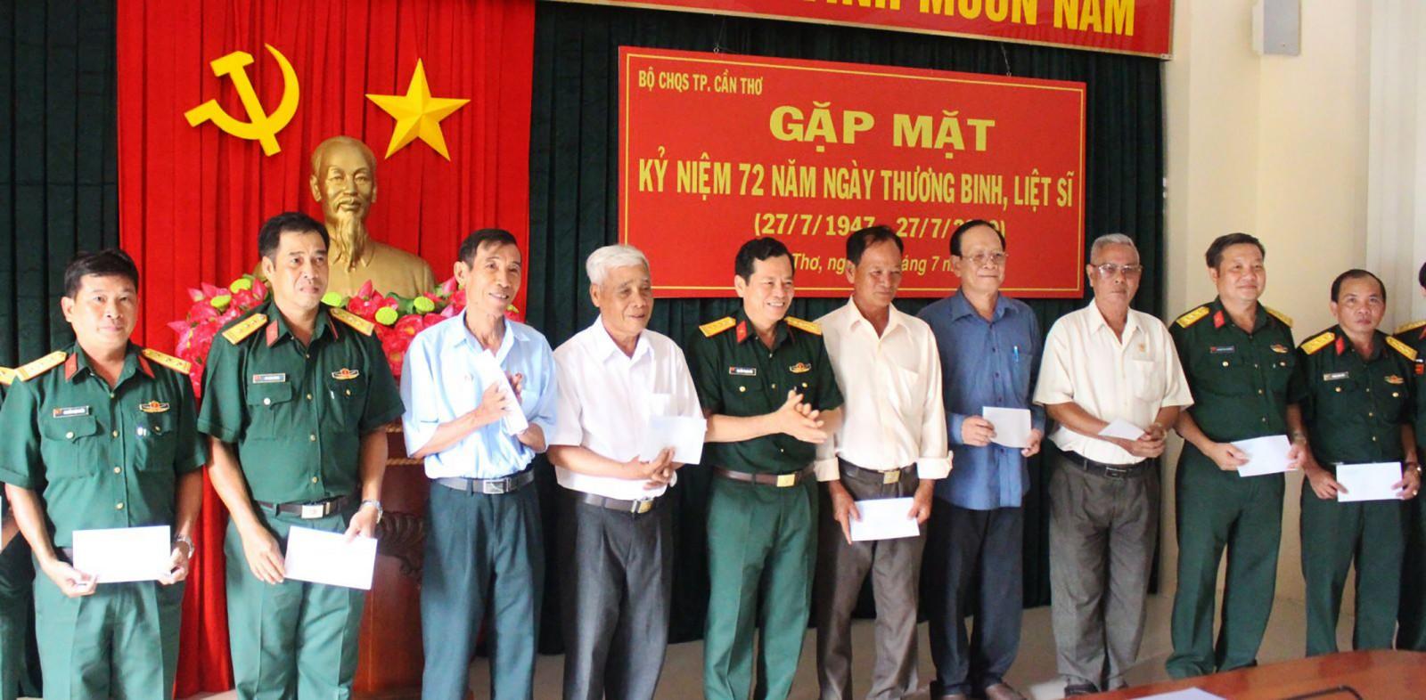 Đại tá Nguyễn Thanh Đức, Chính ủy Bộ CHQS thành phố, trao quà cho cán bộ, chỉ huy Quân sự qua các thời kỳ là thương binh, con liệt sĩ.