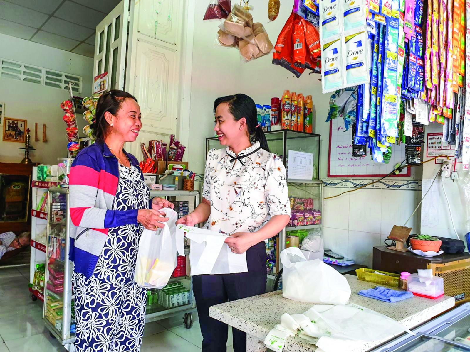 Cán bộ Hội LHPN thị trấn Cờ Đỏ (bên phải) thường xuyên tuyên truyền, vận động chị em tiểu thương cam kết sử dụng túi sinh học trong mua bán thực phẩm.