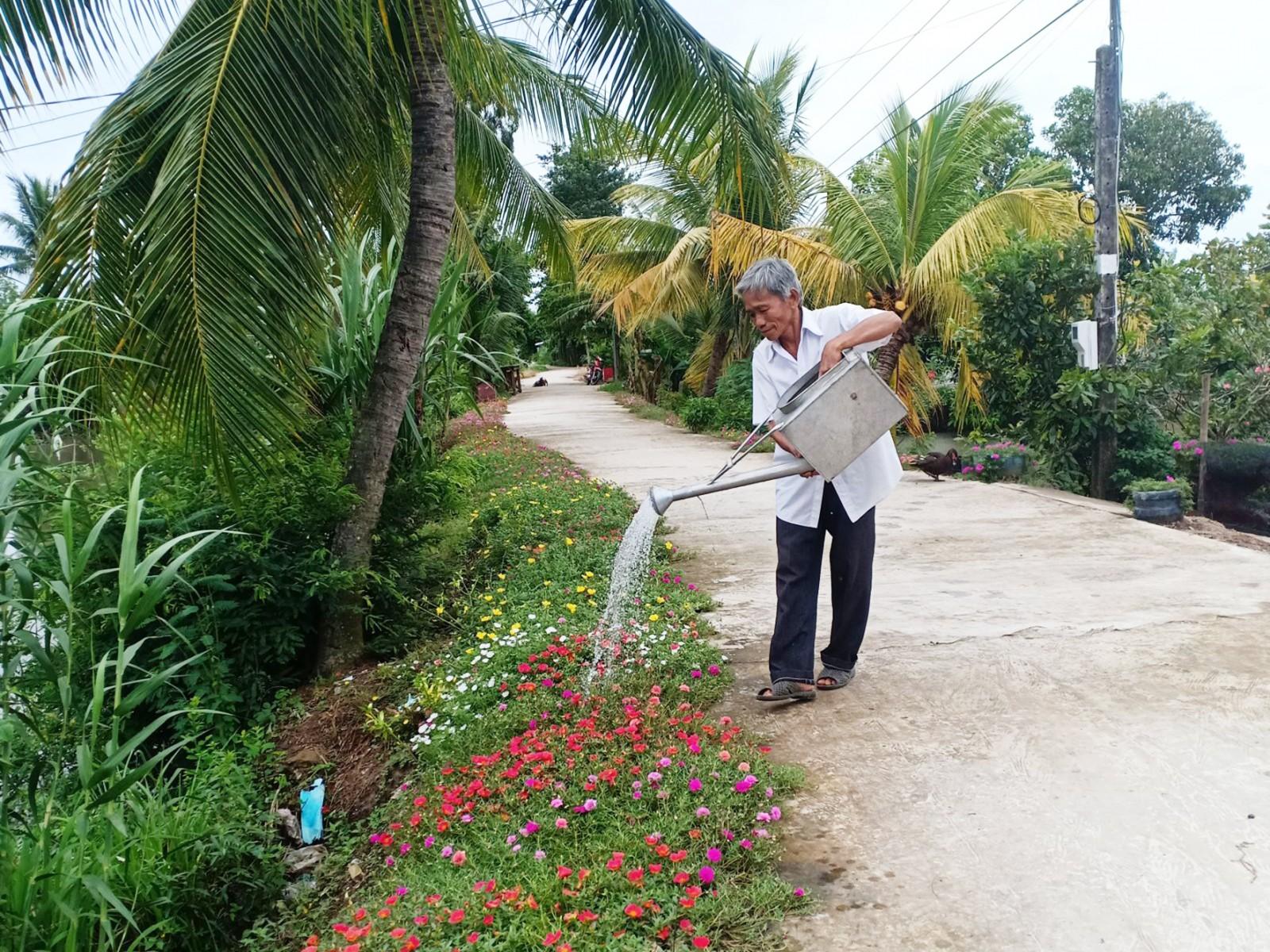 Người dân trồng và chăm sóc hoa kiểng hai bên đường ở kinh Năm Kỵ,  khu vực Thới Hòa C.