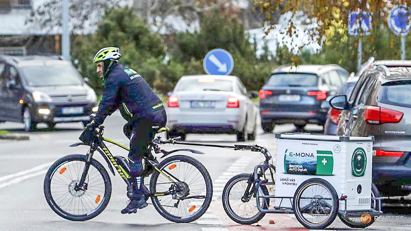 Người đi xe đạp với trạm sạc xe điện nhanh phía sau trên đường phố Prague (Cộng hòa Séc). Ảnh: Reuters