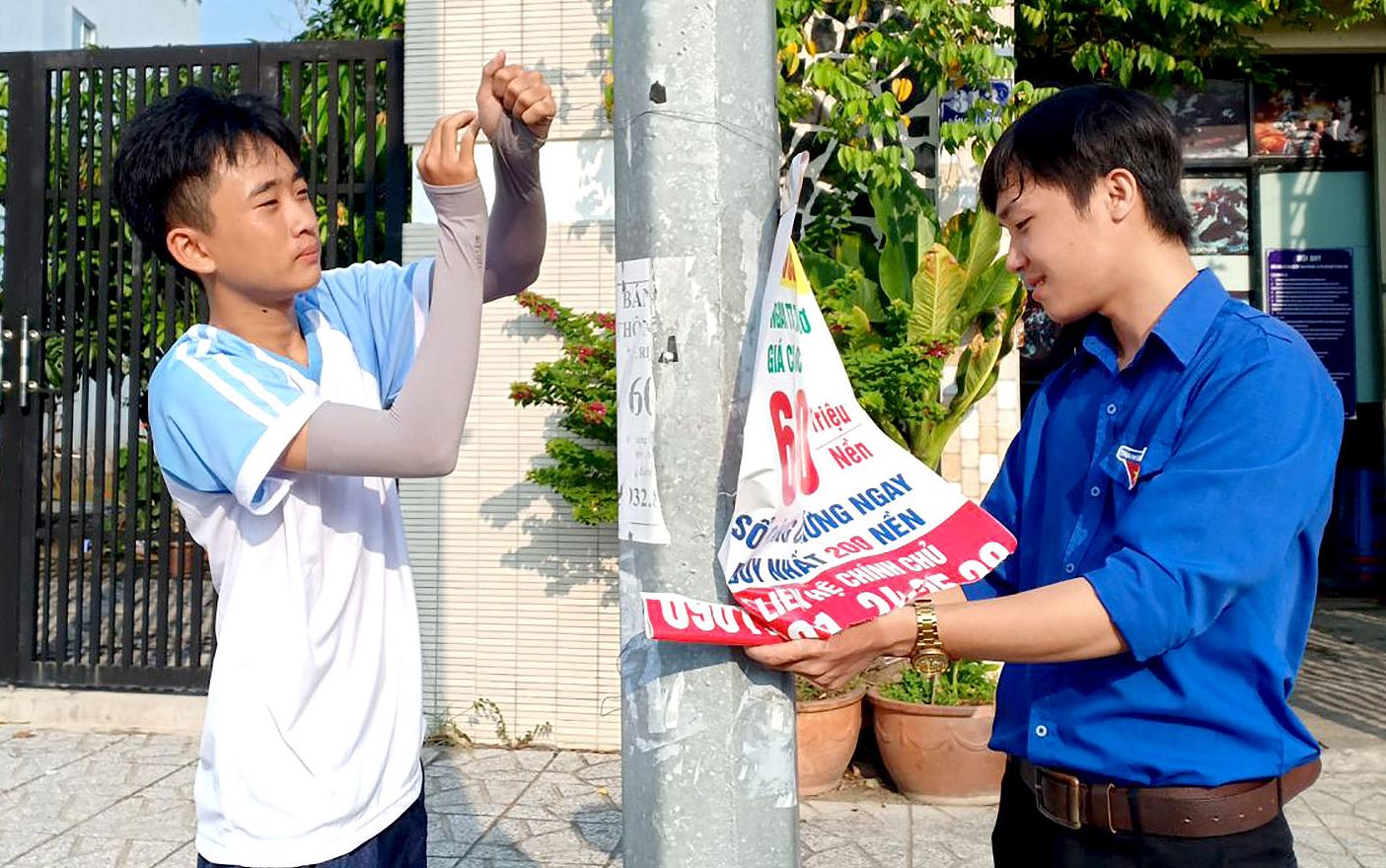 Các bạn đoàn viên tháo dỡ những quảng cáo trái phép trên cây xanh  ở đường Đồng Văn Cống.