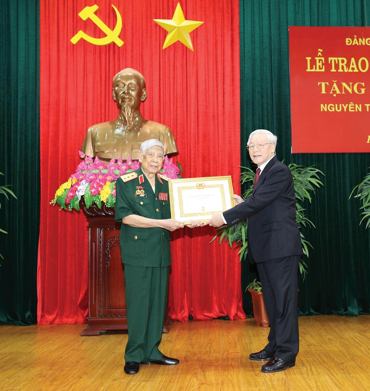 Tổng Bí thư, Chủ tịch nước Nguyễn Phú Trọng, Bí thư Quân ủy Trung ương trao Huy hiệu 70 năm tuổi Đảng tặng đồng chí Lê Khả Phiêu. Ảnh: TRÍ DŨNG – TTXVN