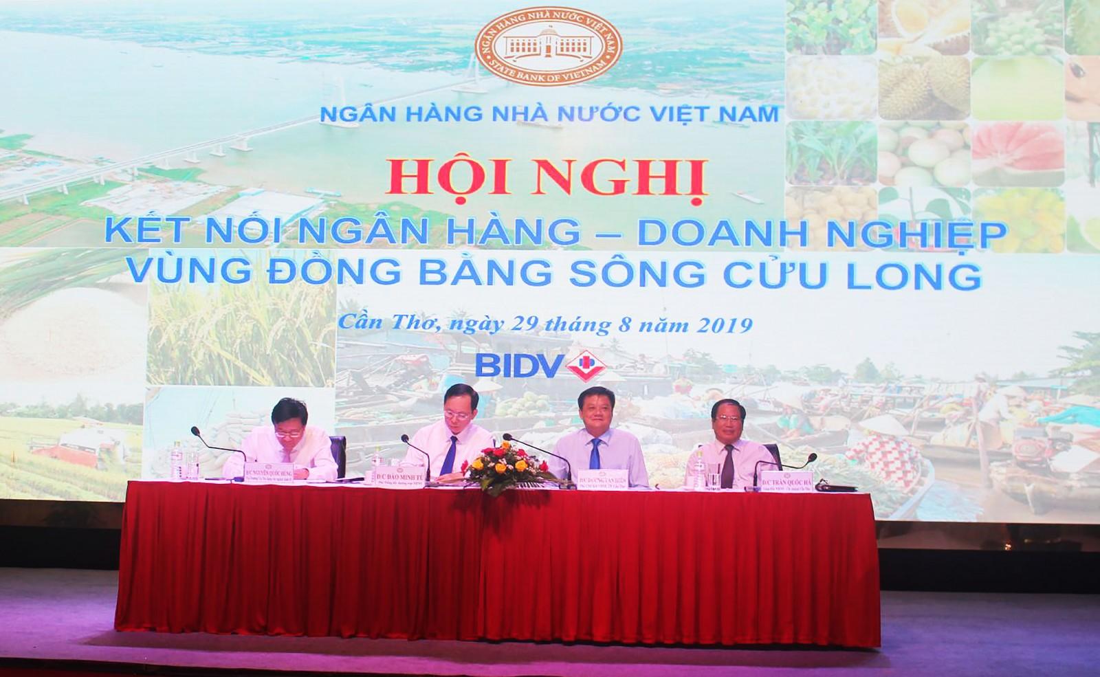 Phó Thống đốc Thường trực NHNN Đào Minh Tú (thứ 2 từ trái sang) chủ trì hội nghị và lắng nghe ý kiến phát biểu từ ngân hàng, doanh nghiệp.