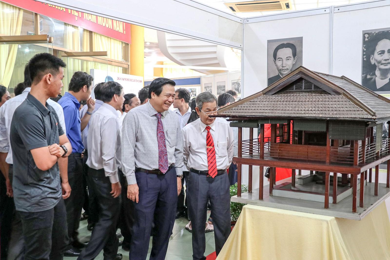 Các đại biểu tham quan mô hình nhà sàn Bác Hồ tại triển lãm.