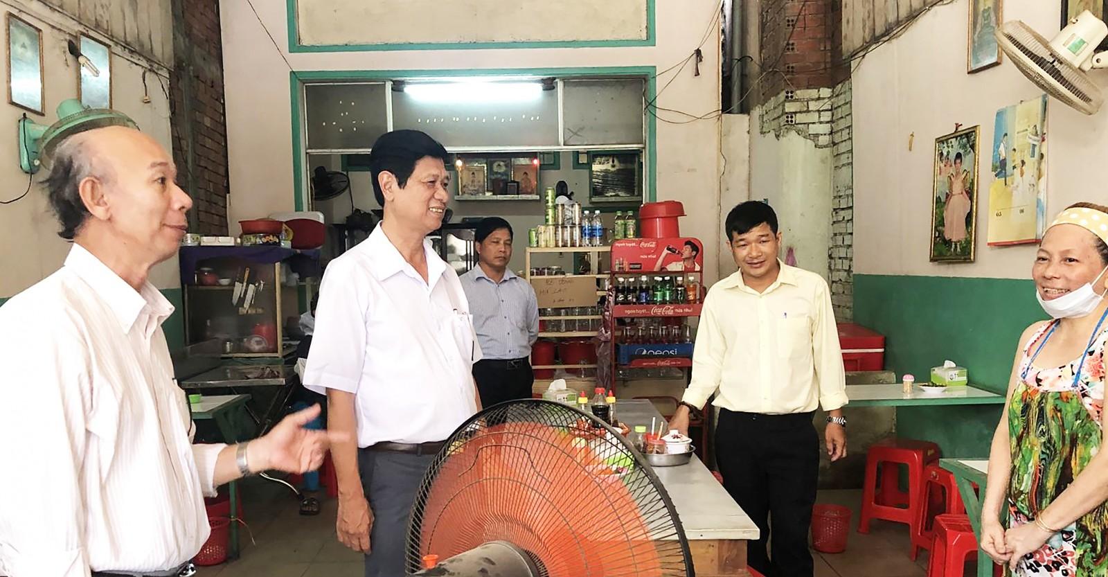 Phó Giám đốc Sở Y tế TP Cần Thơ Huỳnh Văn Nhanh (bên trái, thứ hai), Chi cục An toàn vệ sinh thực phẩm TP Cần Thơ trao đổi với thành viên quán bún riêu Hoa Phượng.