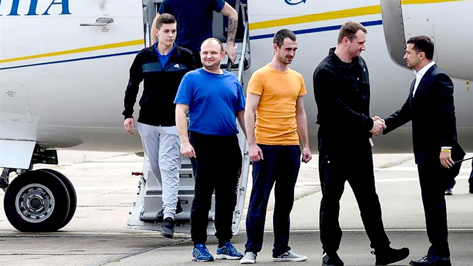 Tổng thống Zelensky (phải) chào đón những người Ukraine được trả tự do khi họ hạ cánh xuống sân bay thủ đô Kiev. Ảnh: AFP