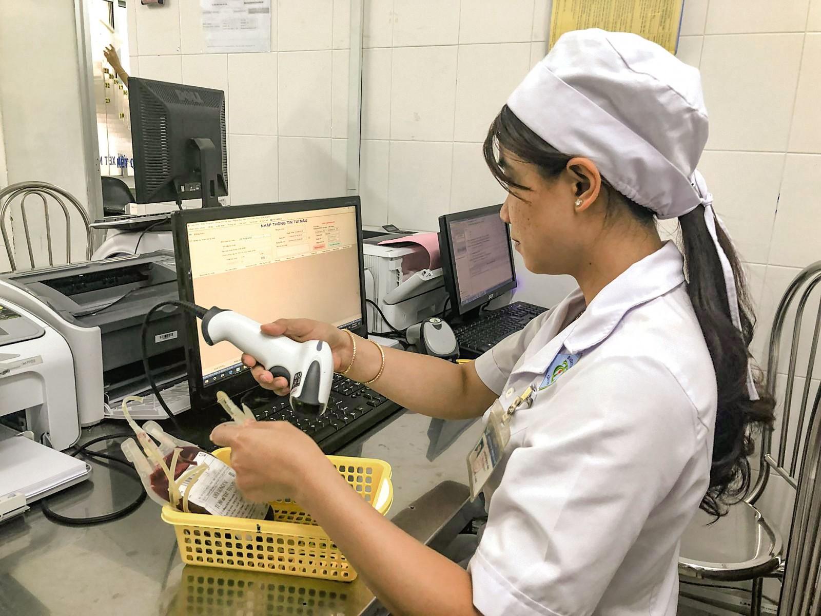 Nhân viên Khoa Huyết học nhập thông tin túi máu vào kho với thao tác quét mã vạch.