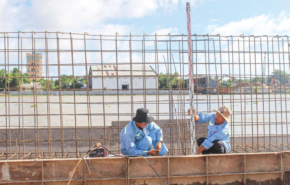 Công nhân trên công trường thi công Dự án Kè bờ sông Cần Thơ ứng phó với biến đổi khí hậu.
