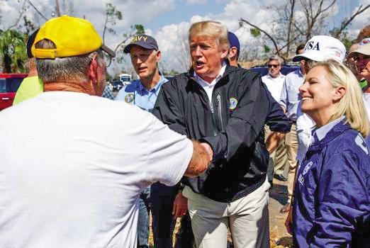 Tổng thống Trump (giữa) bắt tay người dân khi đến thăm Puerto Rico sau siêu bão Maria. Ảnh: AP